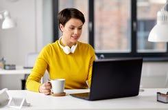 De onderneemster met laptop drinkt koffie op kantoor royalty-vrije stock foto