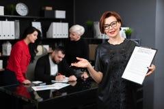 De onderneemster met pen en het contract op achtergrond van beambten bespreken het project stock foto's