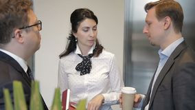 De onderneemster spreekt aan twee haar mannelijke ondergeschikten in de bureaugang dichtbij lift stock footage