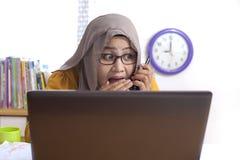 De onderneemster spreekt in het geheim op de Telefoon op het Werk stock foto's