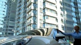 De onderneemster strijkt auto met liefde, aankoop van luxeauto, succes en rijkdom stock foto's