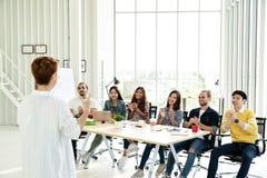 De onderneemster verklaart ideeën zich van creatief divers team op modern kantoor te groeperen Achtermening van manager gesturing royalty-vrije stock fotografie