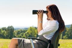 De onderneemster zit in zonnige weide streeft naar binoculair stock foto