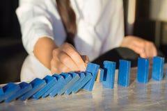 De onderneemsters overhandigen het Tegenhouden van Dalend houten Domino'seffect van ononderbroken omvergeworpen of risico Stock Foto