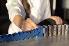 De onderneemsters overhandigen het Tegenhouden van Dalend houten Domino'seffect van ononderbroken omvergeworpen of risico Stock Foto's