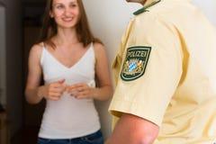 De ondervragingsvrouw van de politieman bij voordeur Royalty-vrije Stock Afbeeldingen