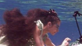 De onderwater model vrije duiker stelt voor camera op achtergrond van koralen in Rode Overzees stock video