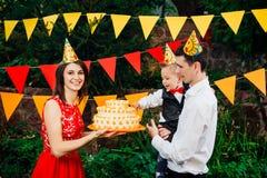 De onderworpen partij van de kinderen` s verjaardag, voedsel en snoepjes Een jonge familie viert één jaar van zoon De papa houdt  royalty-vrije stock afbeeldingen