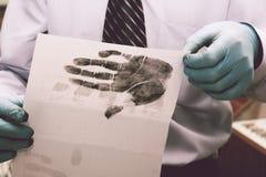 De onderzoeker neemt vingerafdrukken van de verdachte in de misdaad Het onderzoek is een misdaad misdaad stock foto's