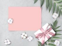De onechte omhoog lege roze document spatie met giftvakje, katoen bloeit en gaat op grijze geweven achtergrond weg royalty-vrije stock foto