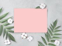 De onechte omhoog lege roze document spatie met katoen bloeit en gaat op grijze geweven achtergrond weg stock fotografie