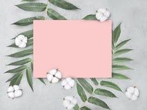 De onechte omhoog lege roze document spatie met katoen bloeit en gaat op grijze geweven achtergrond weg stock afbeeldingen