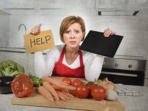 De onervaren vrouw van de huiskok in het rode schort gillen wanhopig en gefrustreerd bij binnenlandse keuken in spanning stock afbeelding