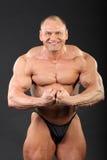 De ongeklede bodybuilder toont wapenspieren aan Royalty-vrije Stock Foto