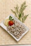 De ongekookte ruwe Garnalen zonder hoofd met citroen snijden en tomaat op witte plaat met mat Bamboe Stock Foto