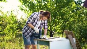 De ongelukkige ambachtenvrouw werpt handschoenen na poging om houten plank met figuurzaag te snijden stock video