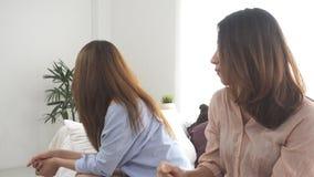 De ongelukkige Aziatische lesbienne lgbt koppelt het zitten van elke kant van bank aan humeurige emotie in woonkamer stock footage