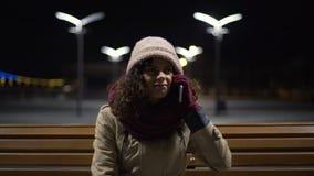 De ongelukkige bevroren meisjeszitting in openlucht, kan geen kerel telefonisch, ontbroken datum bereiken stock footage