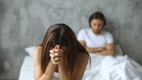 De ongelukkige paarzitting apart op bed, vrouw maakte zich na conflict ongerust stock videobeelden