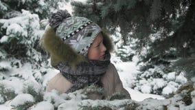 De ongelukkige tribune van het kindmeisje omhoog onder de spar en het stellen, de winter bos, mooi landschap met sneeuwsparren stock footage