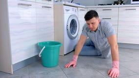 De ongelukkige vermoeide mens in rubberhandschoenen wast de vloer in de keuken en bekijkt aan het eind de camera stock footage