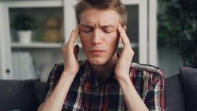 De ongelukkige zieke jonge mens lijdt aan strenge hoofdpijn wat betreft zijn hoofd binnen thuis masserend tempels pijn stock videobeelden