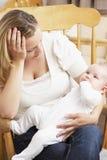 De ongerust gemaakte Baby van de Holding van de Moeder in Kinderdagverblijf Stock Foto's