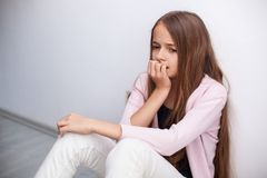 De ongerust gemaakte jonge zitting van het tienermeisje op de vloer door de muur royalty-vrije stock foto