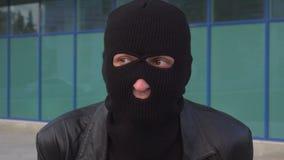 De ongerust gemaakte misdadige mensendief of de rover in masker zijn wachten iets stock footage