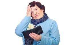 De ongerust gemaakte portefeuille van de gepensioneerdegreep met laatste stuiver Stock Afbeeldingen