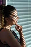 De ongerust gemaakte vrouw denkt en kijkt trogvensters met jaloezies royalty-vrije stock foto
