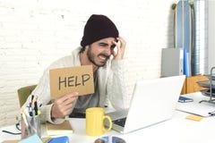 De ongerust gemaakte zakenman in koel hipster beanie kijkt het teken die van de holdingshulp in spannings thuis bureau werken stock afbeelding
