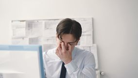De ongerust gemaakte zakenmanwerken met computer in bureau 4K stock videobeelden