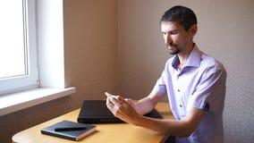 De ongeschoren kerel schrijft sms op het werk stock video