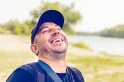 De ongeschoren mens in een GLB lacht met zijn hoofd gehouden hoog stock foto