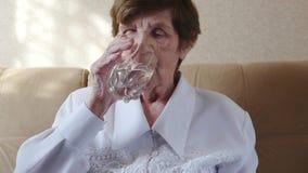 de ongezonde oude vrouw krijgt pillen, drinkt water stock video