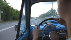 De onherkenbare handen van de mensenholding op stuurwiel en het drijven van zijn oude retro auto op asfaltweg Jonge kerel die a b stock footage