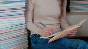 De onherkenbare jonge vrouw schrijft de nota's zittend op de vloer onder de boeken stock videobeelden