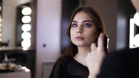 De onherkenbare make-upmeester vult het zwarte luchtpenseel met bruine toner en het toepassen van dunne oppervlakte op het gezich stock videobeelden