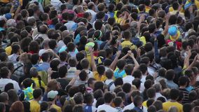 De onherkenbare menigte van mensen heft handen op en geeft applaus stock videobeelden