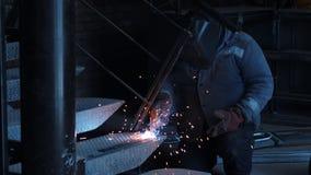 De onherkenbare mens in beschermende kleding en masker bij bouwfabriek is bezig geweest met het lassenwerk Concept van stock videobeelden