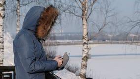 De onherkenbare vrouw in blauw benedenjasje schrijft overseinen in haar cellphone in de winterpark Zachte nadruk stock video
