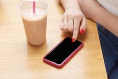 De onherkenbare vrouw gebruikt moderne celtelefoon, houdt vinger met rode spijker op touchscreen, drinkt melkcocktail, spot op he royalty-vrije stock fotografie