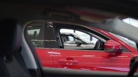 De onherkenbare vrouw in roze jasje loopt dichtbij de auto lopende vingers op automobiele oppervlakte Het schieten van de volgend stock footage