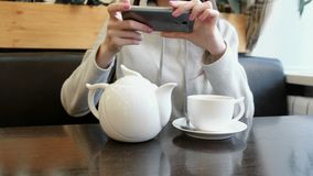 De onherkenbare vrouw ` s overhandigt beelden van theepot en Kop in een koffie op haar celtelefoon stock footage