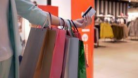 De online betaling, plastic kaart in handen van meisje met velen koopt pakketten in seizoen van kortingen en verkoop stock videobeelden
