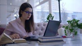De online lessen, studentenmeisje schrijft nota's in notitieboekje en gelezen boekzitting bij lijst met laptop stock footage