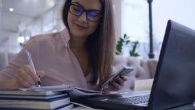 De online lezing, studentenwijfje combineert het werk en studie gebruikend moderne computertechnologie met smartphone en boeken h stock videobeelden