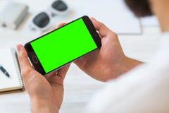 De online plastic betalingskaart de man gebruikt horizontaal een smartphone met a met groen het schermgebruik Royalty-vrije Stock Foto's