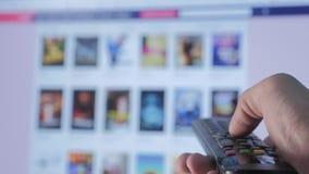 De online video stromende dienst met apps en hand Slimme TV Mannelijke hand die de controledraai houden van slimme TV ver stock footage